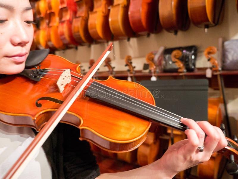 Frauen-Violinist Playing eine Violine in Music Store lizenzfreie stockfotografie