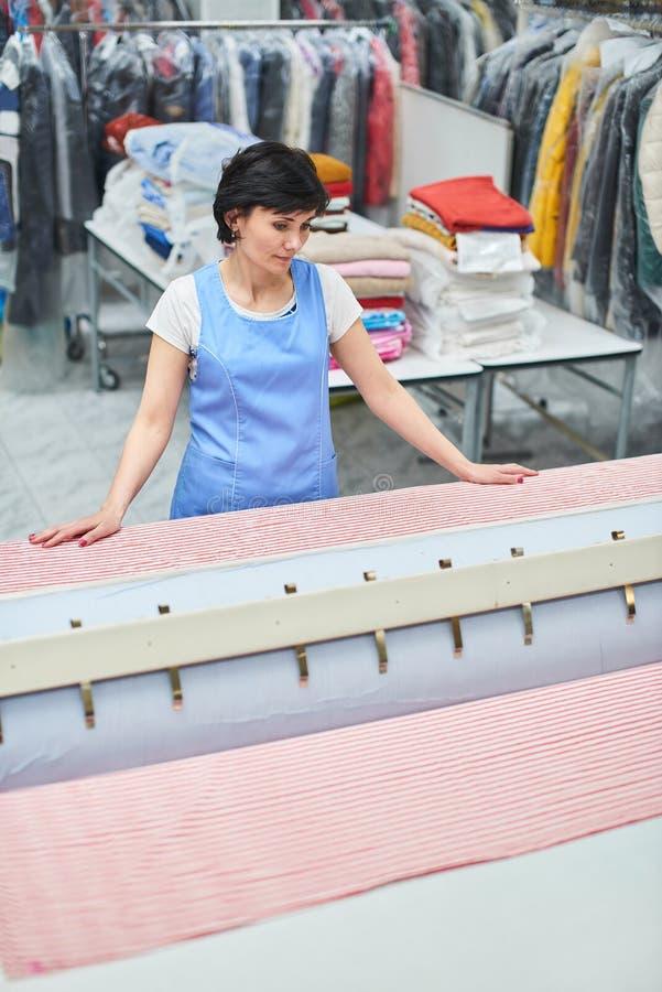 Frauen-Wäschereiarbeitskraft tappt das Leinen auf dem Automaten stockbild