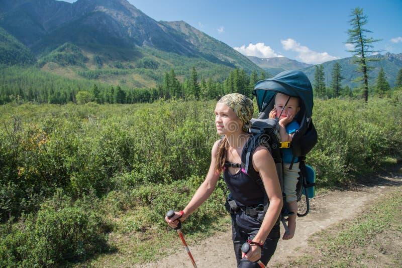 Frauen-Wanderertrekking in den Bergen mit Kind im Rucksack Mutter mit dem Baby, das am sonnigen Tag des Sommers reist lizenzfreies stockfoto