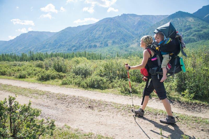 Frauen-Wanderertrekking in den Bergen mit Kind im Rucksack Mutter mit dem Baby, das am sonnigen Tag des Sommers reist stockbilder