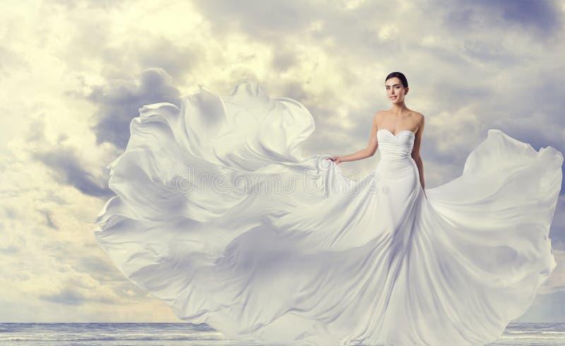 Frauen-weißes Kleid, Mode-Modell in lange Seiden-flatterndem Kleid, wellenartig bewegender fliegender Stoff auf Wind lizenzfreie stockfotografie