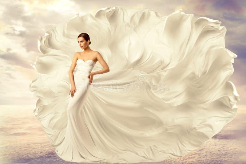 Frauen-weißes Kleid, Mode-Modell in lange Seiden-wellenartig bewegendem Kleid, fliegendes flatterndes Gewebe auf Wind lizenzfreie stockfotos
