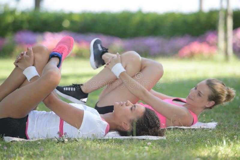Frauen, welche die Beinübungen gelegt auf Gras tun stockfotos