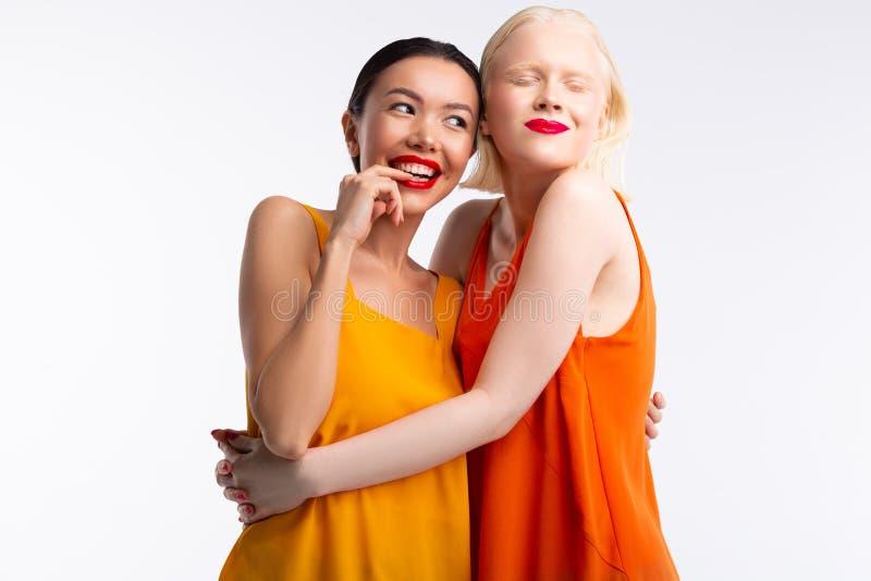 Frauen, welche die hellen Kleider zusammen sich f?hlen wirklich gl?cklich tragen lizenzfreies stockbild