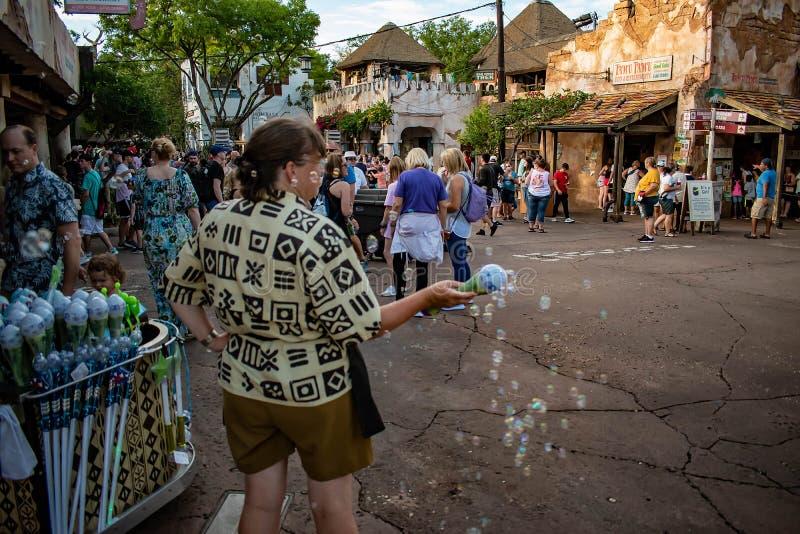 Frauen-wellenartig bewegender glühender Blasen-Stab im Tierreich an Walt Disney World-Bereich stockfotografie