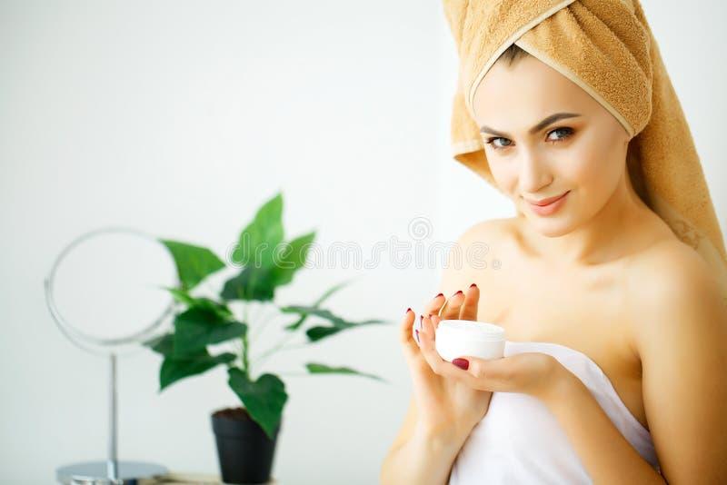Frauen wenden Creme und Lotion an ihrem Gesicht an, nach herein baden lizenzfreie stockfotografie