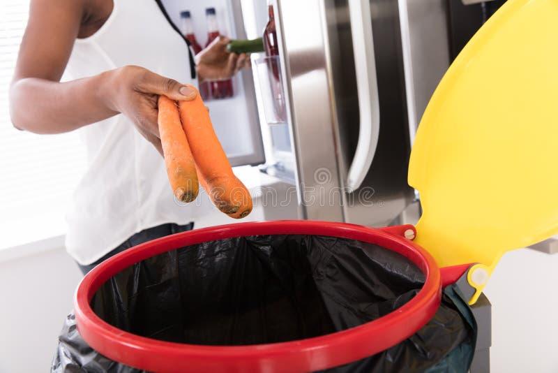 Frauen-werfende Karotte im Abfalleimer lizenzfreies stockbild