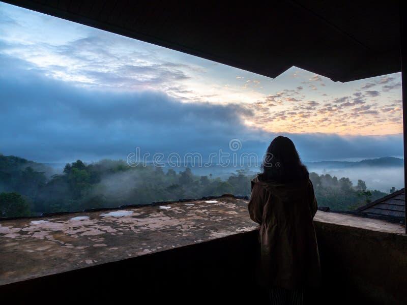 Frauenabnutzungsbraunmantel und -stellung auf dem Balkon Und Blick draußen mit Wald und Nebel morgens Die goldene Sonne ist hinte stockbilder