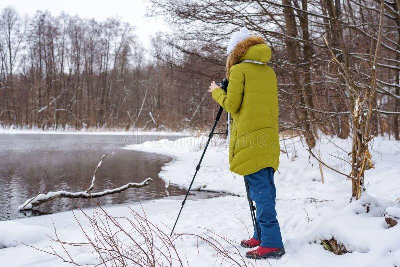 Frauenamateurphotograph nimmt eine Winterlandschaft auf dem See im Waldkopienraum stockbilder