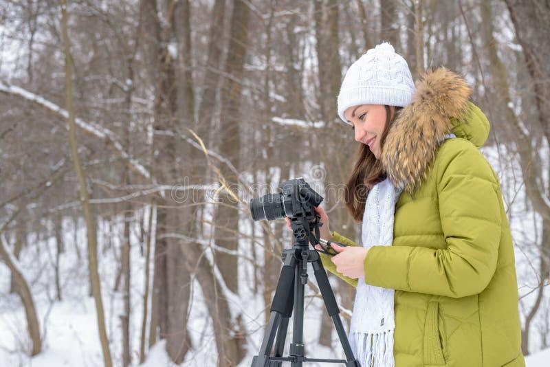 Frauenamateurphotograph nimmt eine Winterlandschaft auf dem See im Waldkopienraum lizenzfreies stockbild