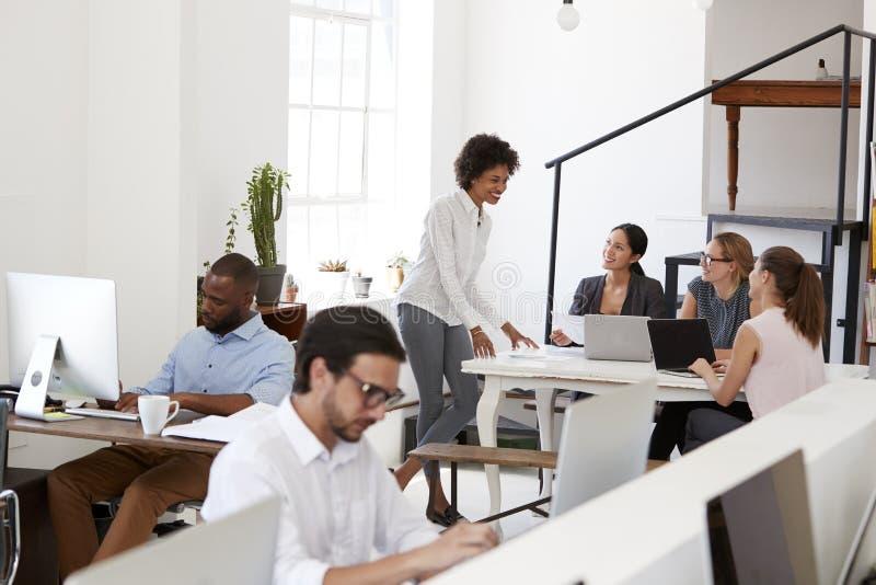Frauenanweisungskollegen um einen Schreibtisch im Bürogroßraum lizenzfreie stockfotos