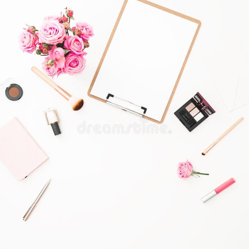 Frauenarbeitsplatz mit rosa Rosenblumenstrauß, -kosmetik, -tagebuch und -klemmbrett auf weißem Hintergrund Beschneidungspfad eing lizenzfreies stockfoto