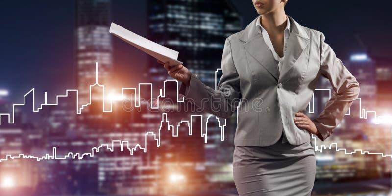Frauenarchitekt oder -ingenieur, die Baukonzept darstellen und in der Hand Dokumente verwahren lizenzfreies stockfoto