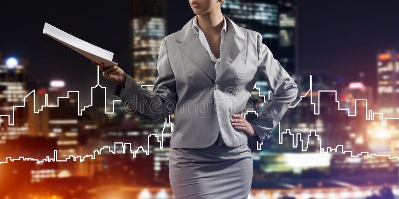 Frauenarchitekt oder -ingenieur, die Baukonzept darstellen und in der Hand Dokumente verwahren stockfoto