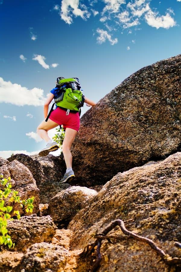 Frauenaufstiege über einem Felsen stockfotografie