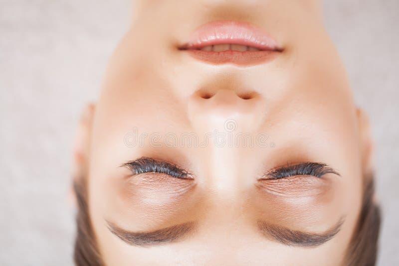 Frauenauge mit den langen Wimpern Sch?ne junge Frau w?hrend der Wimpererweiterung stockfoto