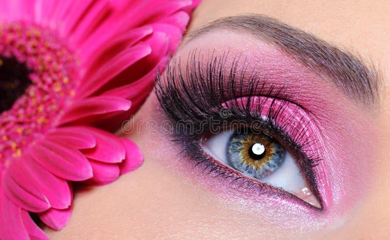 Frauenauge mit rosafarbener Verfassung und Blume lizenzfreie stockfotografie