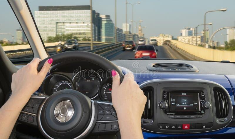 Frauenautofahren auf der Straße, die zu die Stadt führt lizenzfreie stockfotografie