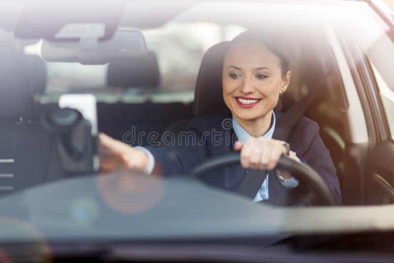 Frauenautofahren und -c$l?cheln stockfoto