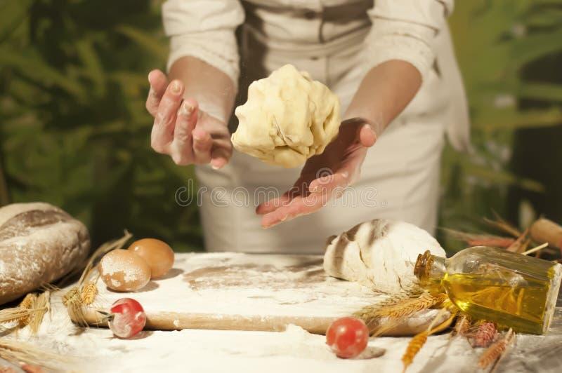 Frauenbäckerhände, Pizza knetet Teig und die Herstellungshausarbeit, die Brot, Butter, Tomatenmehl macht lizenzfreie stockfotos