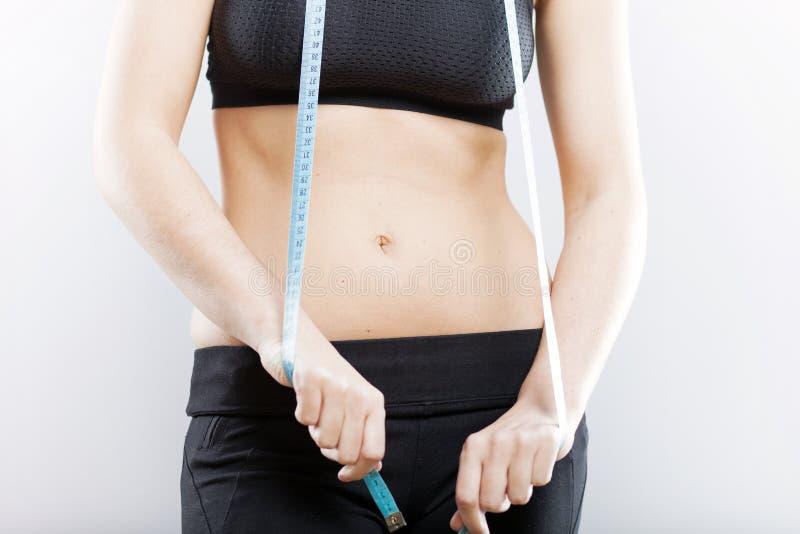 Frauenbauch und messendes Band, Gewichtsverlustkonzept lizenzfreies stockfoto