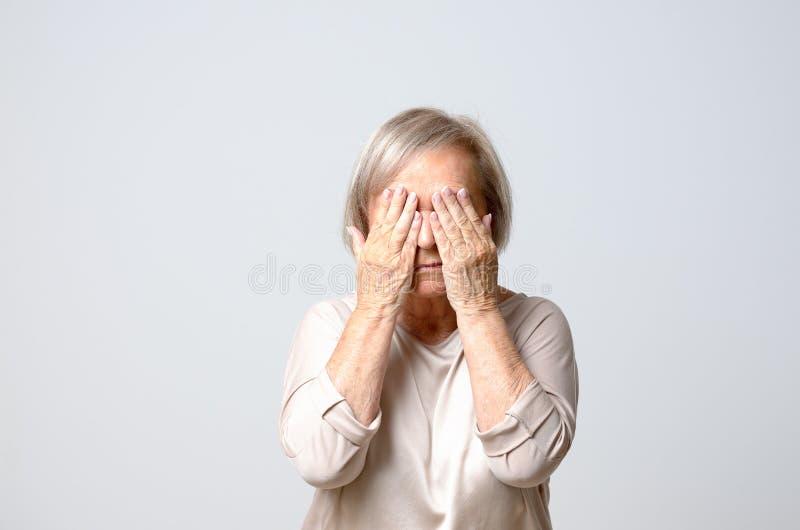 Frauenbedeckungsaugen mit ihren Fingern stockfotografie