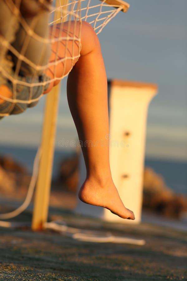 Frauenbein, das auf Hängematte auf dem Strand sich entspannt lizenzfreie stockfotos
