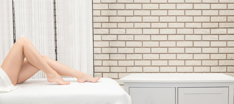 Frauenbeine, die zu Hause auf einem Haar-Abbaukonzept der Couch sitzen lizenzfreies stockfoto
