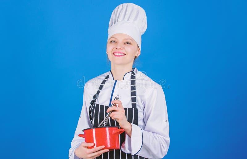 Frauenberufschefgriffschneebesen und -topf Peitschen wie Pro M?dchen im Schutzblech Eier oder Creme peitschend Anfang langsam lizenzfreies stockbild