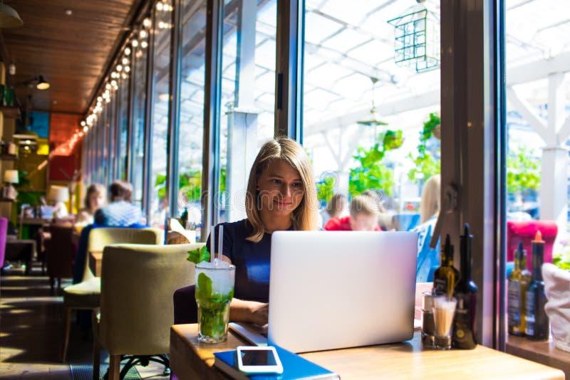 Frauenberufsverfasser, der an dem netbook, sitzend mit Getränk in der Kaffeestube arbeitet lizenzfreies stockbild