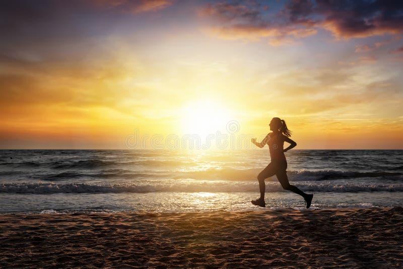 Frauenbetrieb auf dem Strand während der Sonnenuntergangzeit lizenzfreie stockfotografie