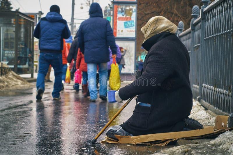 Frauenbettler mit Spazierstock bitten um Geld auf Moskau-Straße im Winter stockfoto