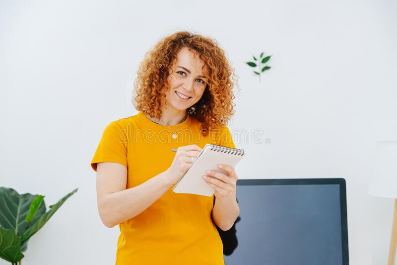 Frauenbildportrait auf ihrem Notizblock mit Risscreme, Lächeln bei der Kamera lizenzfreies stockfoto