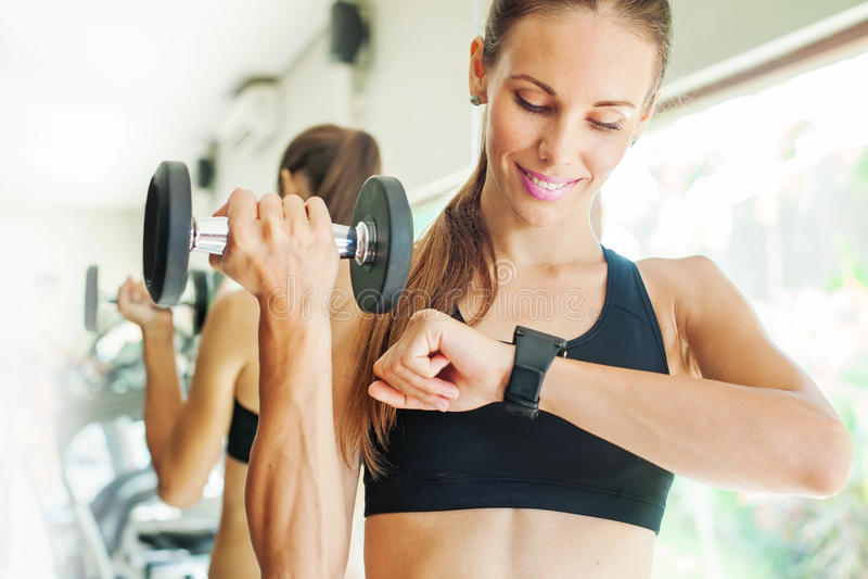 Frauenblick auf ihre intelligente Uhr für Herzschlagrate lizenzfreies stockbild