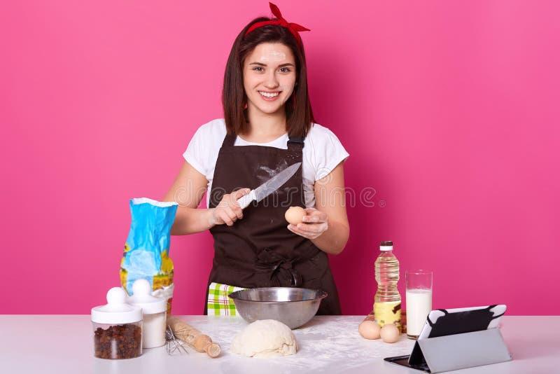 Frauenbremsen ärgern mit Messer, setzt es in Platte des Mehls, benötigt mehr Teig für die Zubereitung von heißen Querbrötche stockbilder