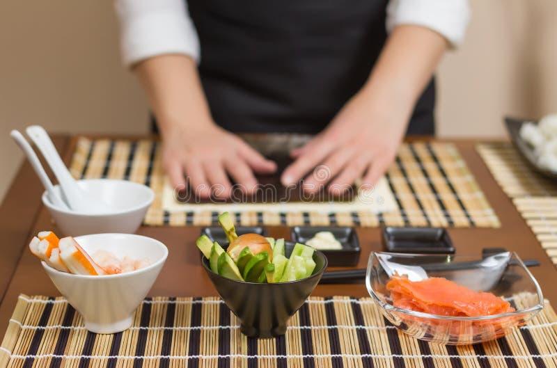 Frauenchef bereit, japanische Sushirollen vorzubereiten stockbilder