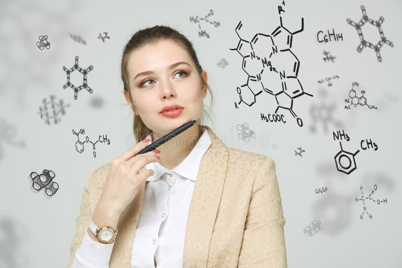 Frauenchemiker, der mit chemischen Formeln auf grauem Hintergrund arbeitet stockfotografie