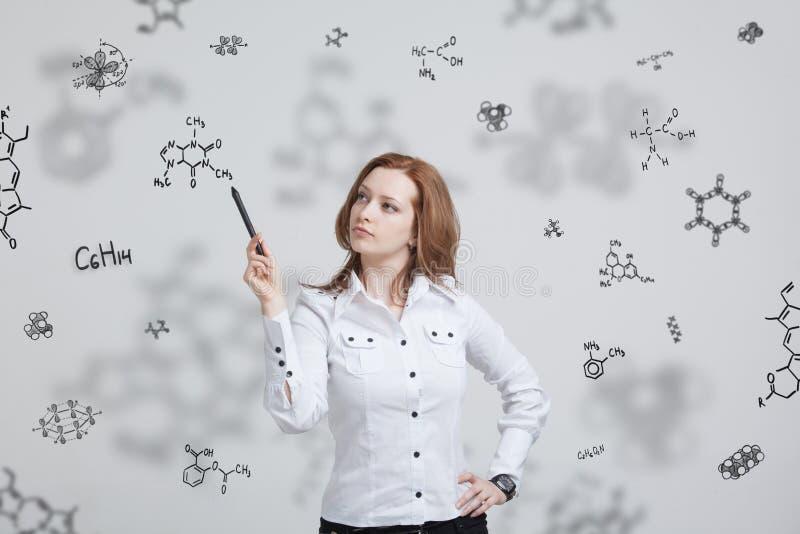 Frauenchemiker, der mit chemischen Formeln auf grauem Hintergrund arbeitet stockfotos