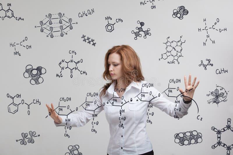 Frauenchemiker, der mit chemischen Formeln auf grauem Hintergrund arbeitet lizenzfreie stockfotografie