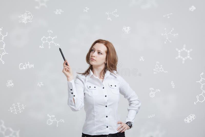 Frauenchemiker, der mit chemischen Formeln auf grauem Hintergrund arbeitet lizenzfreie stockfotos