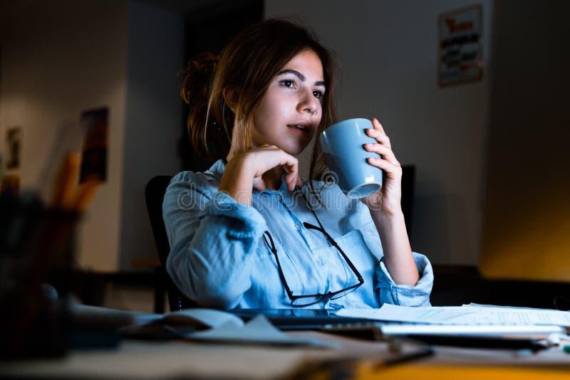 Frauendesigner, der in arbeitendem trinkendem Kaffee oder Tee des Büros nachts sitzt lizenzfreies stockbild