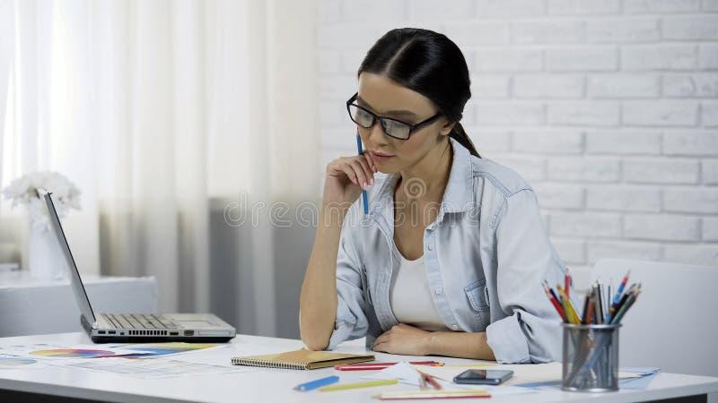 Frauendesigner, der zu Hause über Projekt, Telearbeit, Stilist von Kleidung denkt lizenzfreie stockfotos