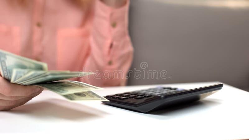 Frauendollar in der Hand Steuern, Taschenrechner zählend auf Tabelle, Finanzinvestition stockfoto