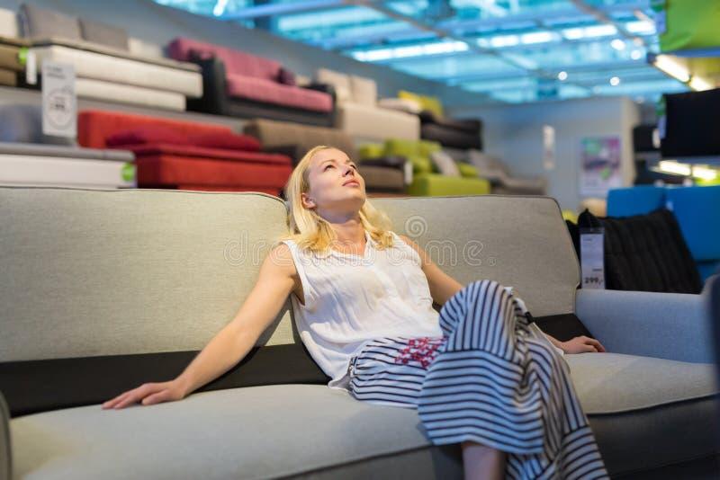 Fraueneinkaufen für Möbel, Sofa und Hauptdekor im Speicher stockfotografie