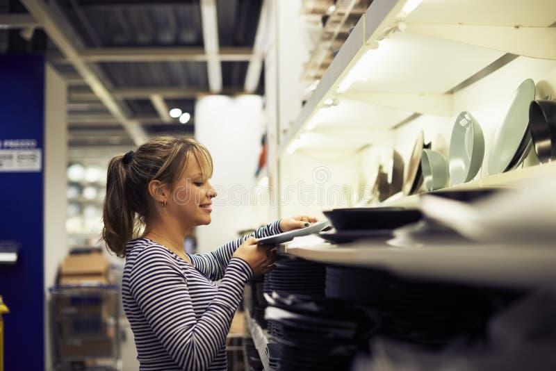 Fraueneinkaufen für Möbel und Hauptdekor lizenzfreie stockbilder