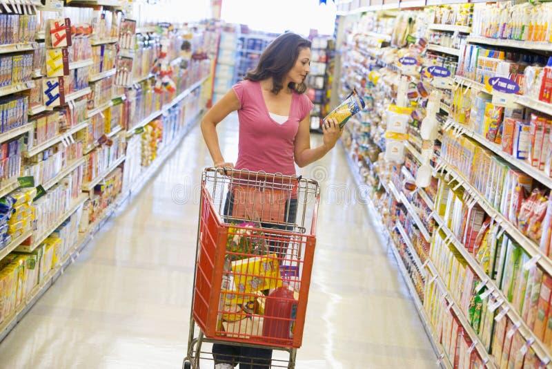 Fraueneinkaufen im Supermarktgang stockbilder