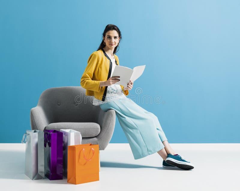 Fraueneinkaufen und Ablesen einer Modezeitschrift lizenzfreie stockfotos