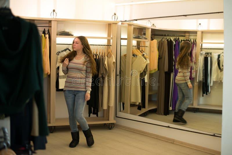 Fraueneinkaufen, welches die Kleider schauen im Spiegel unsicher wählt stockfotos