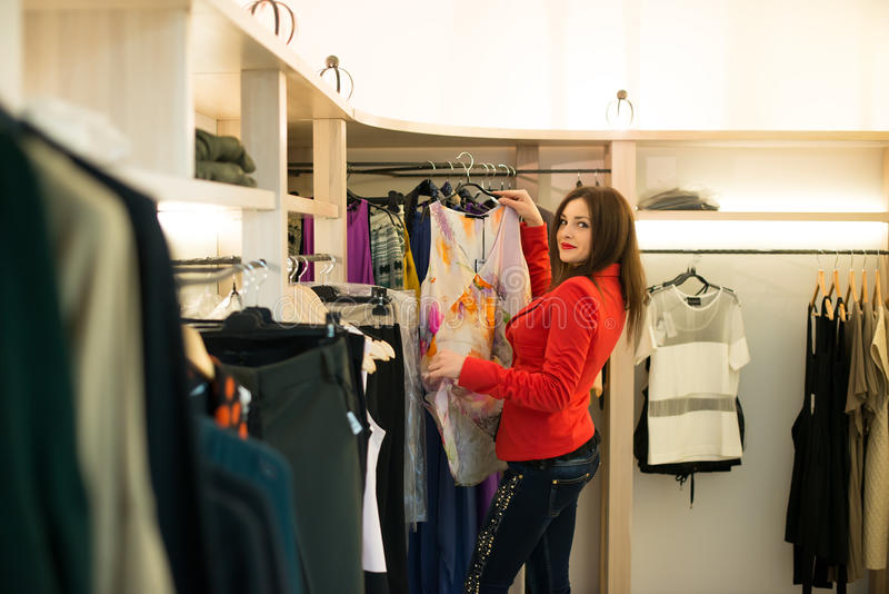 Fraueneinkaufen, welches die Kleider schauen im Spiegel unsicher wählt lizenzfreies stockfoto