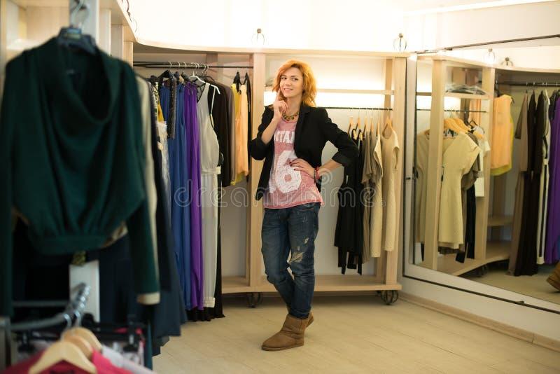Fraueneinkaufen, welches die Kleider schauen im Spiegel unsicher wählt stockfoto